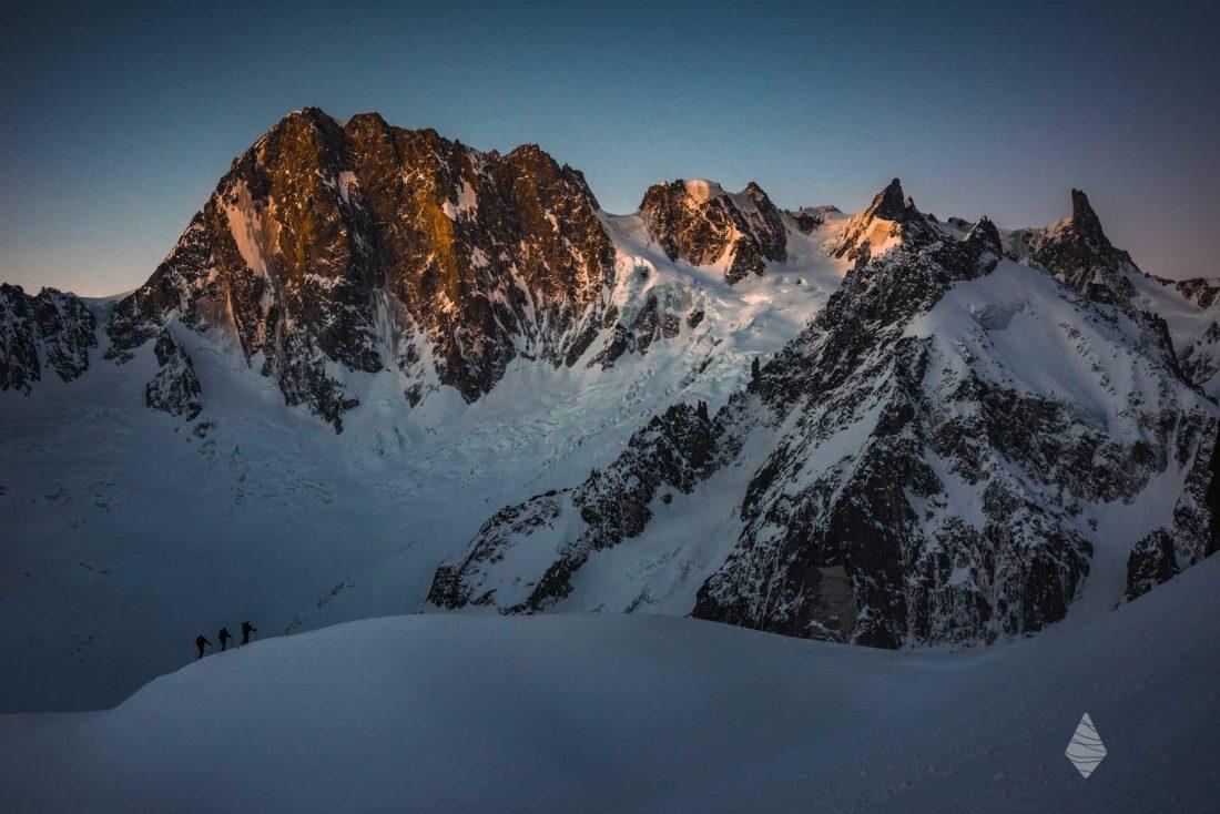 Photo de ski de randonnée dans le Massif du Mont-Blanc avec les Grandes Jorasses en arrière plan illuminées par les premières lueurs du jour