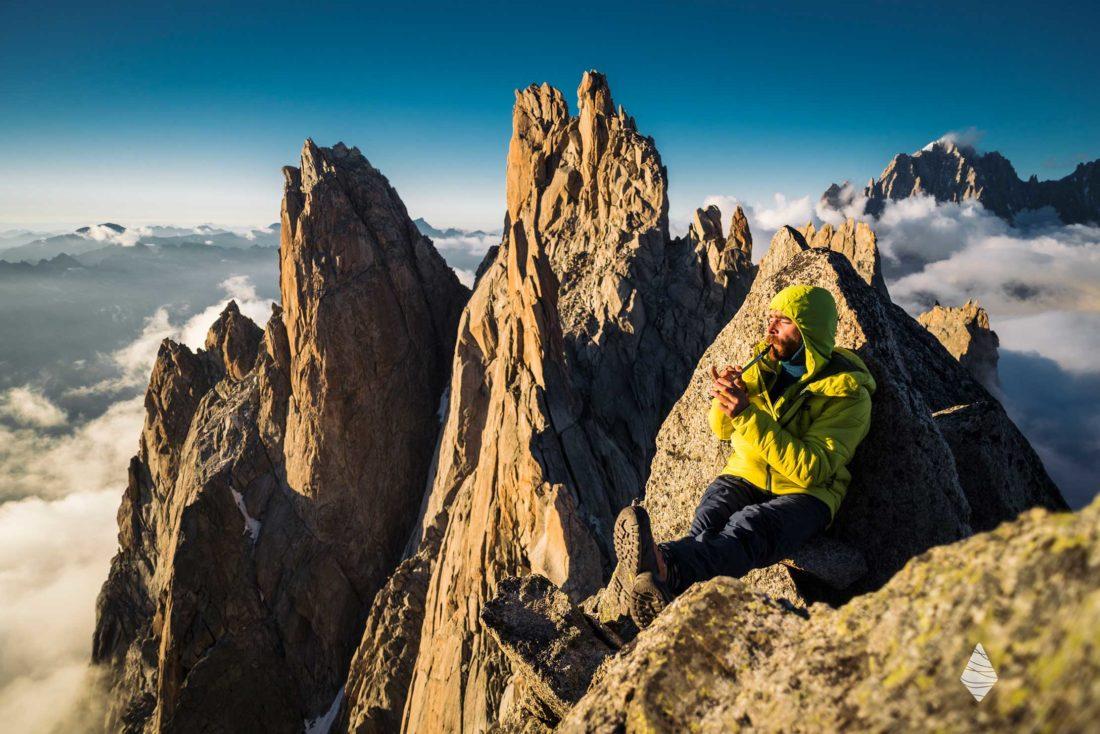 Photo de Sean Villanueva O'Driscoll avec sa flute au sommet de l'Aiguille du Fou dans le Massif du Mont-Blanc.