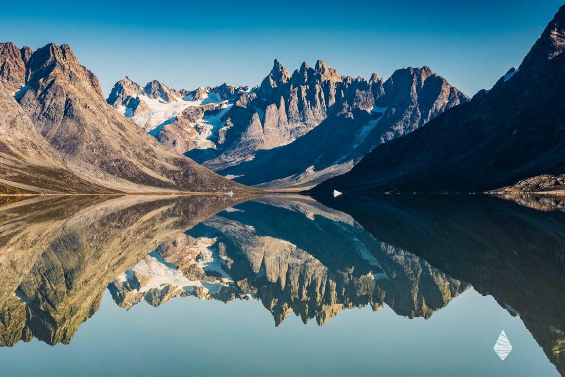 Photo du Fjord Tasiilaq au Groenland avec le reflet des montagnes Fox Jaws dans l'eau
