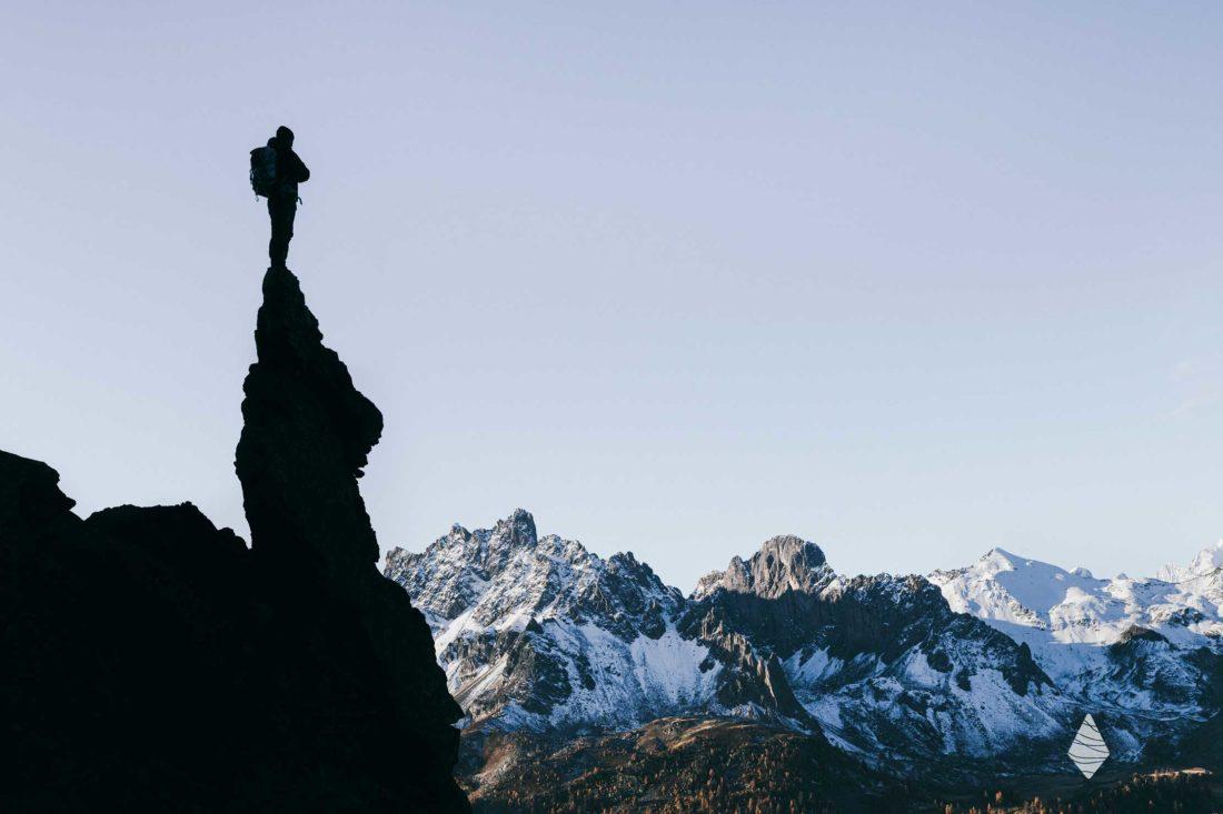 Photo d'une silhouette au sommet d'un bloc rocheux en train de contempler le Massif des Ecrins.