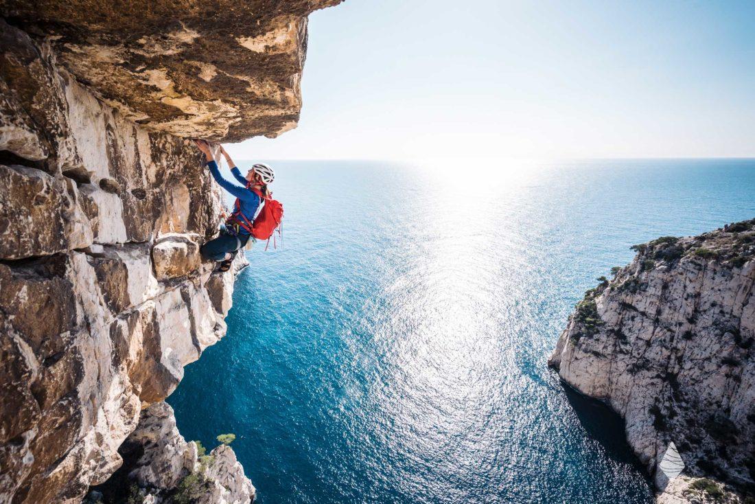Photo d'une grimpeuse dans un surplomb des Calanques au dessus de la Mer Méditerrannée.