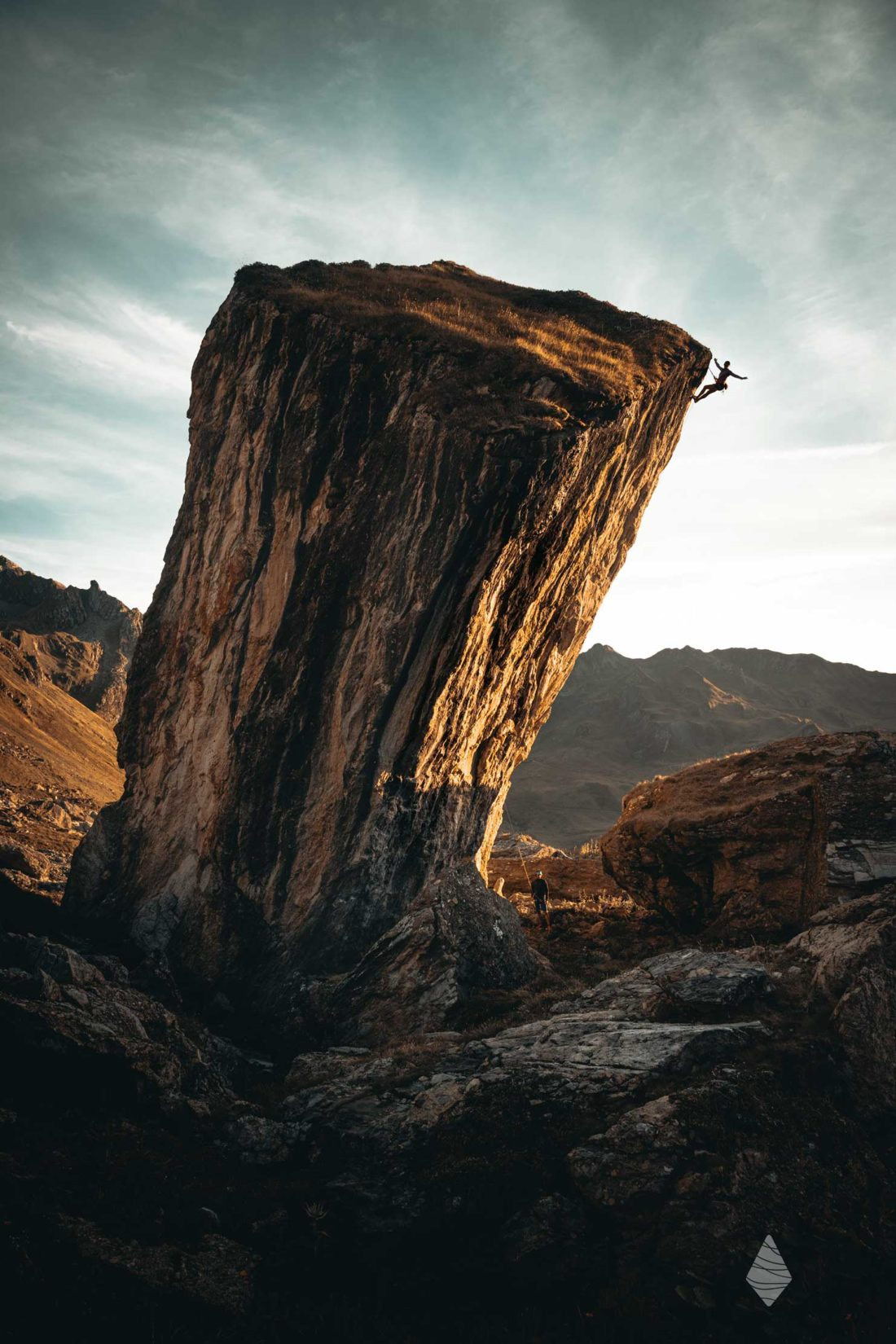 Photo du bloc monolithe avec un grimpeur au sommet