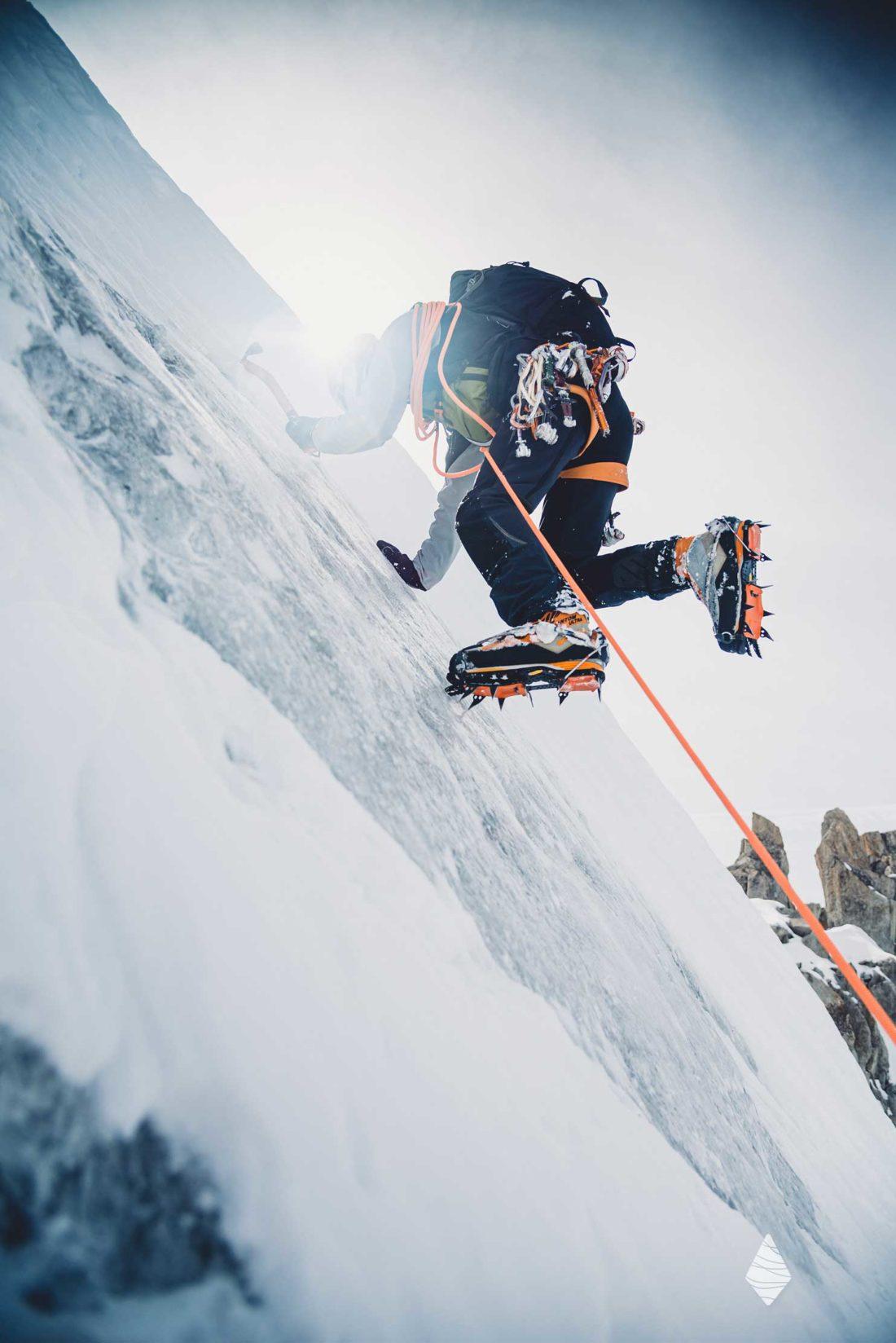 Photo d'un alpiniste en terrain de remonter un mur de glace. On voit l'utilisation des crampons.