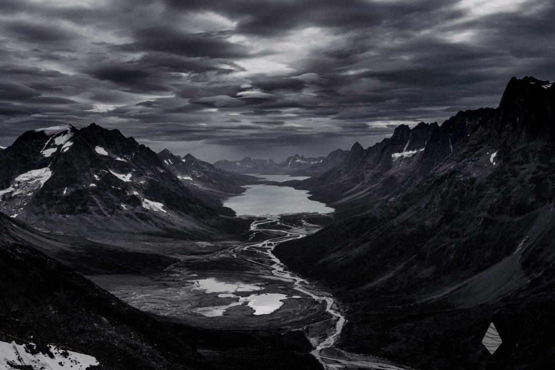 Photo en noir et blanc d'un fjord au Groenland avant un orage.