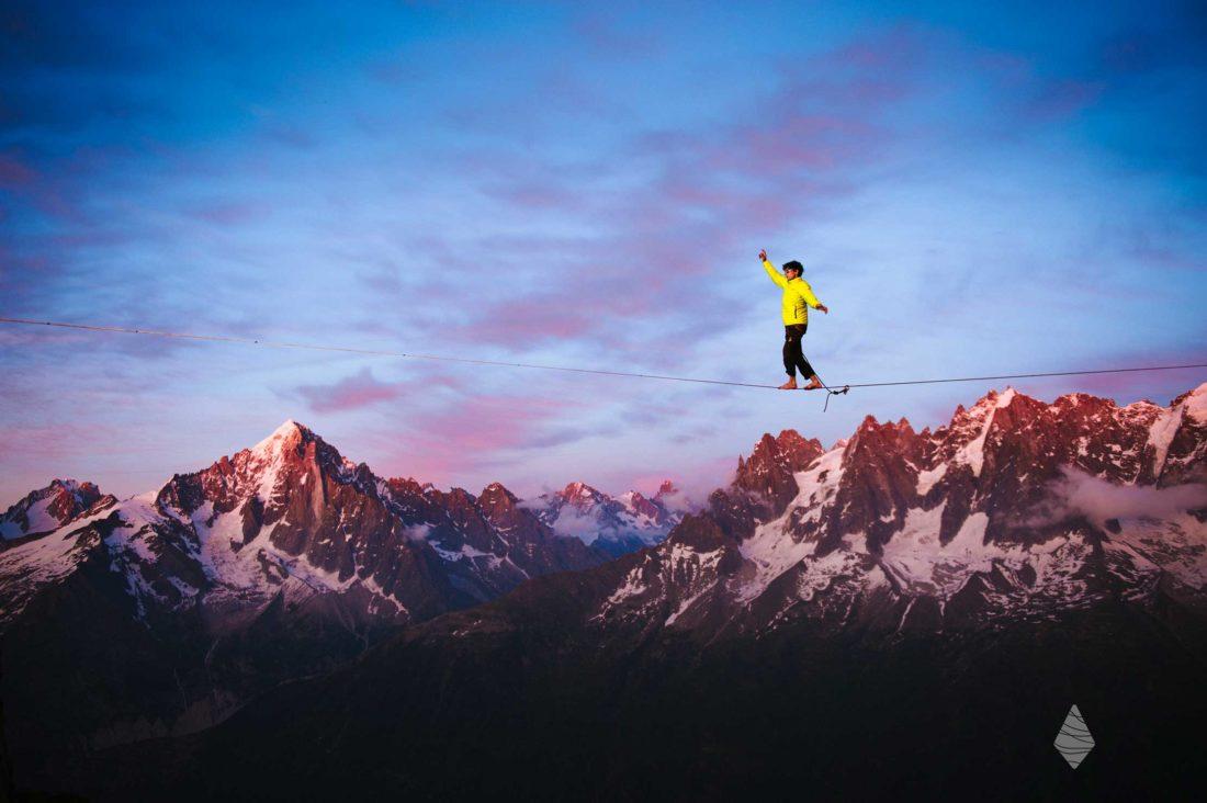 Photo de highline avec le Massif du Mont-Blanc en arrière plan au coucher de soleil.