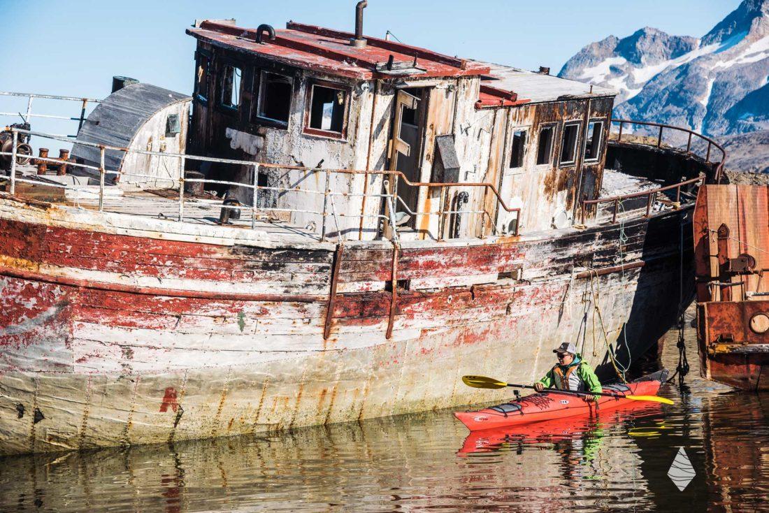 Photo d'un kayakiste de mer devant une vieille épave de bateau en bois au Groenland