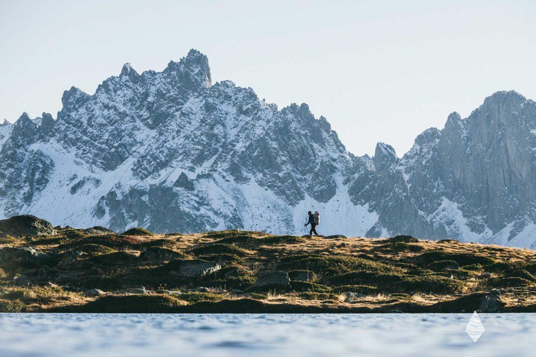Photo d'un randonneur devant des montagnes enneigées dans la vallée de la Clarée dans les Hautes-Alpes.