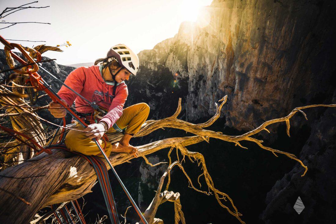 Photo d'une grimpeuse assise sur la branche d'un arbre en pleine paroi des Gorges du Verdon.