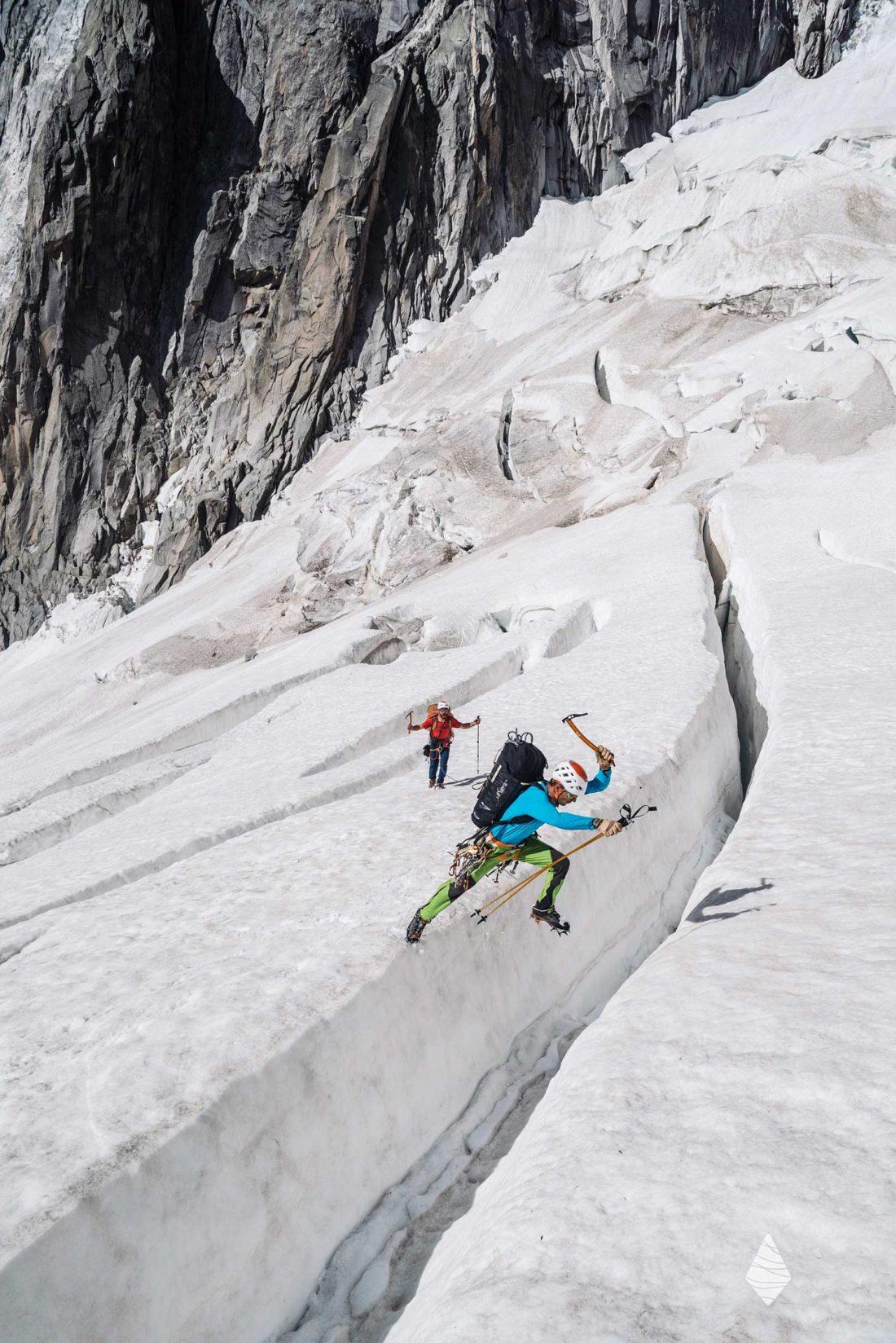 Photo d'un alpiniste en train de sauter une crevasse dans le Massif du Mont-Blanc