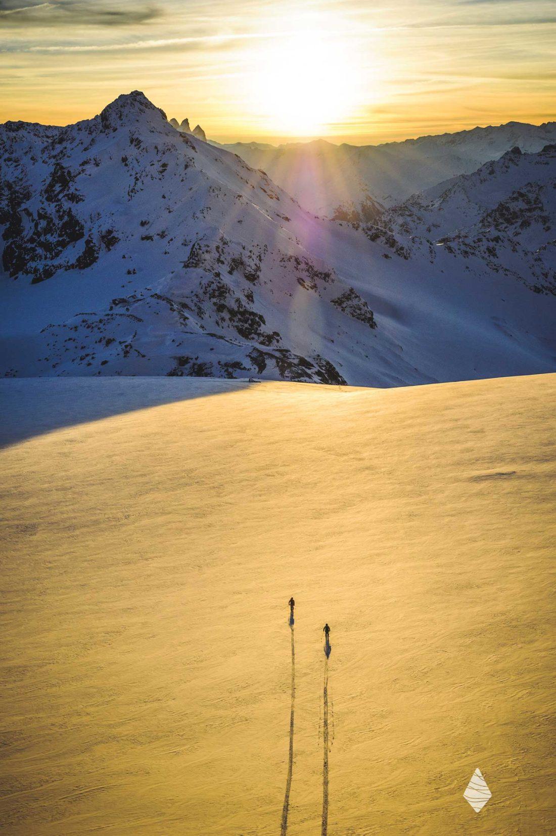 Photo des skieurs au coucher de soleil