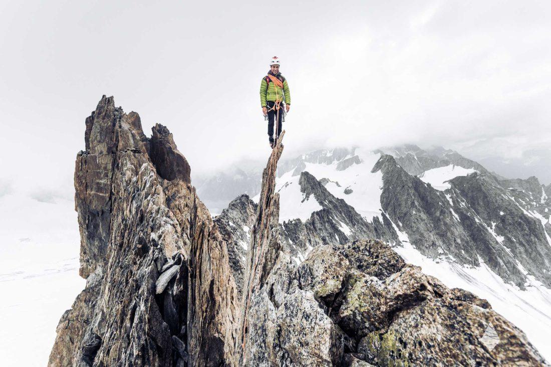 Photo d'un alpiniste en équilibre sur une aiguille de granite dans le Massif du Mont-Blanc