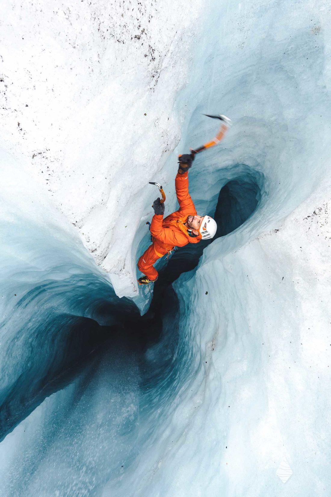 Photo d'un grimpeur entrain de remonter en escalade un moulin dans le glacier de la Mer de Glace